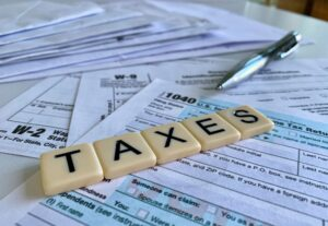 Low angle of letter tiles with the word TAXES on a variety of tax forms.