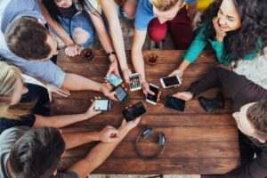 Top view hands circle using phone in cafe - Multiracial friends